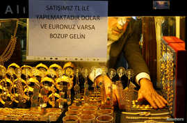 A goldsmith arranges wristbands at a shop at the Grand Bazaar in Istanbul, Turkey, Dec. 5, 2016. The sign on the window reads: Our sales are in Turkish Lira. If you have Dollar or Euro, come after exchange.