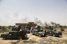 Smoke rises from Islamic State positions as Iraqi federal police take combat positions at the front line during fight against IS outside Fallujah, May 28, 2016.