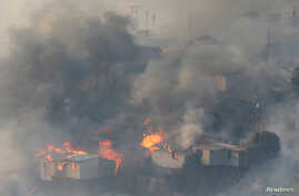 Fire burns houses on a hill, where more than 100 homes were burned due to a forest fire but there have been no reports of death, local authorities said in Valparaiso, Chile Jan. 2, 2017.