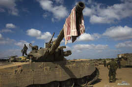 An Israeli soldier stands on a tank outside the northern Gaza Strip, July 26, 2014.