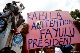 Supporters of the runner-up in Democratic Republic of Congo's presidential election, Martin Fayulu, hold up a sign ahead of a political rally in Kinshasa, DRC, Jan. 11, 2019.