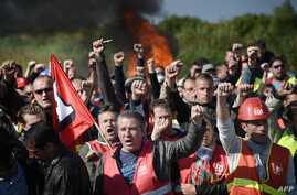 Workers on strike are evacuated by French riot policemen as they block the access to an oil depot near the Total refinery of Donges, western France, to protest against the government's planned labour law reforms on May 27, 2016.