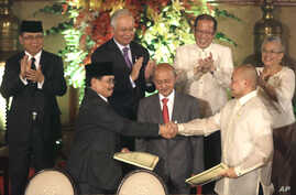 Government peace negotiator Marvic Leonen (R) and Moro Islamic Liberation Front chief negotiator Mohagher Iqbal (L) shake hands as they exchange signed peace documents following formal signing ceremony at Malacanang Palace in Manila, Philippines, Oct