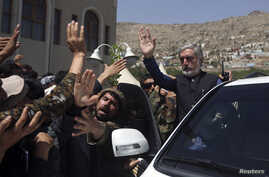 Afghan presidential candidate Abdullah Abdullah (R) waves after a ceremony commemorating the 2001 assassination of legendary Tajik resistance commander Ahmad Shah Massoud, in Kabul, September 9, 2014.