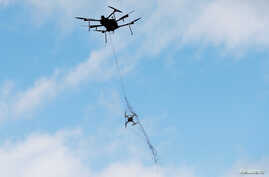 An Airspace Systems Interceptor autonomous aerial drone releases a kevlar net to capture a simulated hostile drone during a product demonstration in Castro Valley, California, March 6, 2017.
