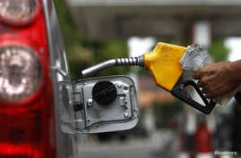 A worker fills a tank with subsidized fuel at a fuel station in Jakarta, April 18, 2013.