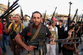 FILE - Iraqi Shiite tribal fighters deploy with their weapons while chanting slogans against the al-Qaida-inspired Islamic State of Iraq and the Levant, in Baghdad's Sadr City, Iraq, June 13, 2014.