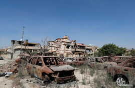 Burnt cars are seen next to buildings damaged during clashes between military forces loyal to Libya's eastern government and the Shura Council of Libyan Revolutionaries, an alliance of former anti-Gadhafi rebels who have joined forces with the Islami