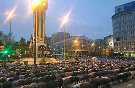 In this citizen journalism image acquired by The AP, Syrians pray in Clock Square in the center of the city of Homs, Syria, April 18 2011
