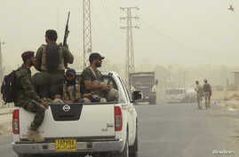 Armed Shi'ite volunteers from brigades loyal to radical cleric Muqtada al-Sadr, travel in a vehicle before taking their positions during a patrol after clashes with militants of the Islamic State, formerly known as the Islamic State in Iraq and the L