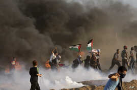 Protesters run to cover from teargas fired by Israeli troops, while others burn tires near fence of Gaza Strip border with Israel, during a protest east of Gaza City, Friday, Sept. 7, 2018. A teenager was killed and dozens of other Palestinians injur
