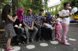 Syrian refugees Halima Taha, second from left, and her husband Fadi Sayed Ahmad, third from left, talk with another Syrian migrant family during the school festival of their children of the elementary school in the village Golzow, about 80 kilometers