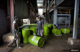 FILE - Workers are seen pushing barrels of vegetable oil.