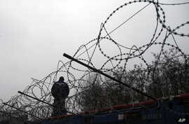 "A Hungarian police officer stands guard at Serbia's border with Hungary near a makeshift camp for migrants in Horgos, Serbia, Wednesday, Feb. 8, 2017. European Commission Vice-President Frans Timmermans said Wednesday that it is ""highly urgent"" for c"