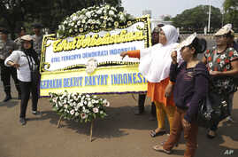 Protesters hold a placard during a rally, opposing a regional election bill in front of palace in Jakarta, Monday, Sept 29, 2014.
