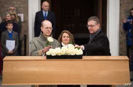 Canadian carpenter Michael Ibsen, left, a descendant of King Richard III, the last of the Plantagenet dynasty, and two other descendants place roses on the oak coffin with the remains of the monarch during a service in Leicester, England, March 22, 2