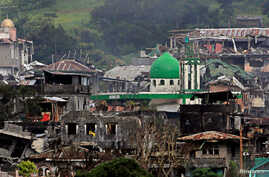 Damaged buildings and houses are seen as government forces continue their assault against insurgents from the Maute group, who have taken over large parts of Marawi city, Philippines, June 22, 2017.