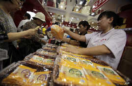 FILE - A vendor, right, sells mooncakes to a customer, left, at a shop in Shanghai, China.