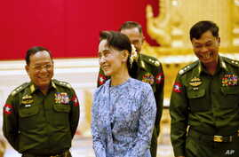Myanmar's NLD party leader Aung San Suu Kyi smiles with army members during the handover ceremony of outgoing President Thein Sein and new President Htin Kyaw at the presidential palace in Naypyitaw March 30, 2016. REUTERS/Ye Aung Thu/Pool      TPX I