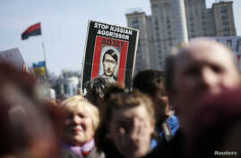 People hold a sign depicting Russian President Vladimir Putin as Adolf Hitler as they attend a unity rally at Independence Square, in Kyiv, Ukraine, March 23, 2014.