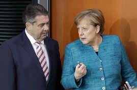German Chancellor Angela Merkel, right, and German Foreign Minister Sigmar Gabriel, left, arrive for the weekly cabinet meeting at the Chancellery in Berlin, April 12, 2017.