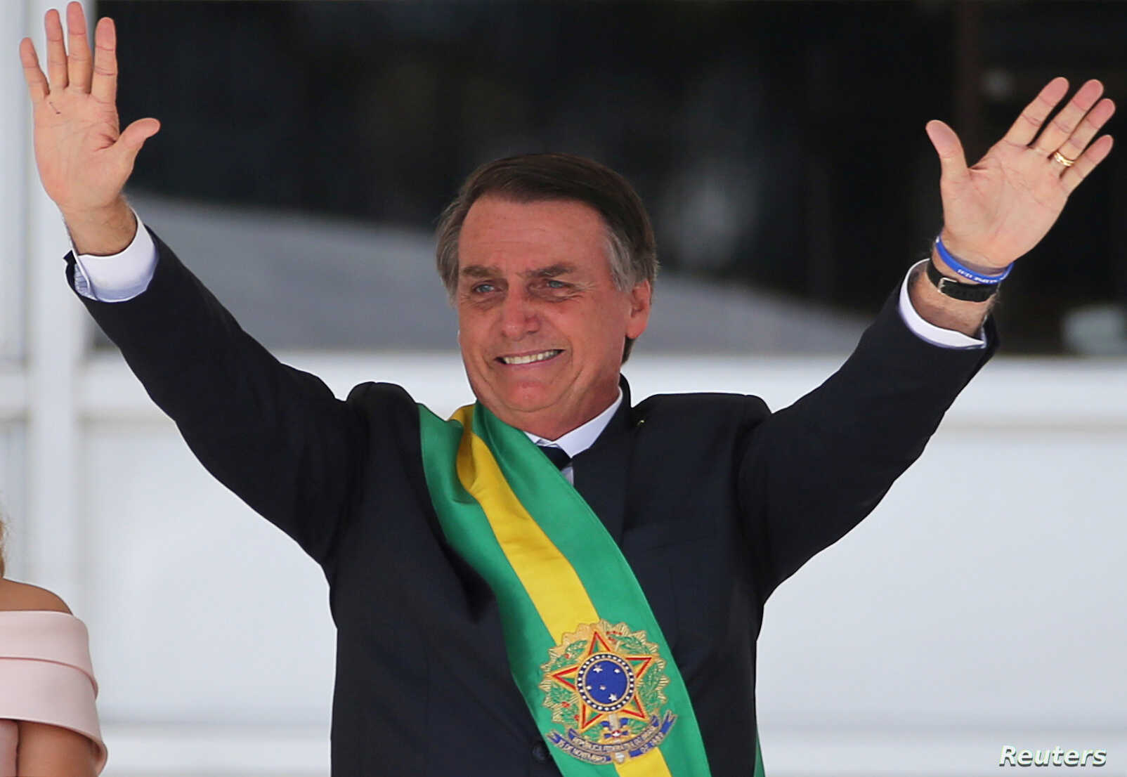 FILE - Brazil's new President Jair Bolsonaro gestures after receiving the presidential sash from outgoing President Michel Temer at the Planalto Palace, in Brasilia, Brazil, Jan. 1, 2019.