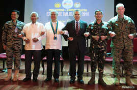 Philippines and U.S. officials link arms during the opening ceremony of the 2016 Balikatan military exercises at the Armed Forces of the Philippines (AFP) headquarters in Camp Aguinaldo, Quezon city, metro Manila April 4, 2016.