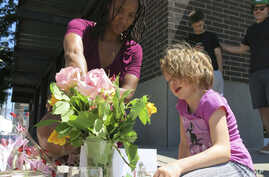 Angel Sauls (left) helps her stepdaughter, Coco Douglas, arrange a sign and some painted rocks she made for a memorial in Portland, Ore., May 27, 2017, for two bystanders who were stabbed to death Friday while trying to stop a man who was yelling ant...