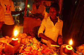 A Ugandan woman shops at  a kiosk in candle light in Kampala. (file photo)