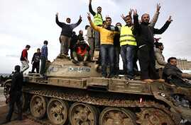 Anti-government protesters make victory signs as they stand on an army tank in Benghazi, February 24, 2011