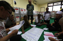 Election commission official Dedi Saidi, left, reads document stating the number of votes collected in ballot boxes, Bendungan Hilir, Jakarta, July 10, 2014.