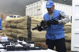 In this photo released by the U.N. mission based in Colombia, a member of U.N. monitoring mission for the Colombian peace process holds a weapon handed over by FARC rebels, as part of last year's peace agreement in Colombia, June 13, 2017.