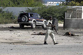 Somali police officers walk past bodies of two civilians who were killed during a suicide-bomb attack targeting Mogadishu international airport, 09 Sep 2010