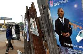 A man walks past an election poster for incumbent President Laurent Gbagbo, as presidential campaigning kicked off, 15 Oct. 2010 in Abidjan, Ivory Coast