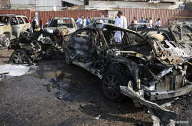 Iraqis inspect the site of a car bomb attack in Basra, southeast of Baghdad, Sept. 30, 2014.