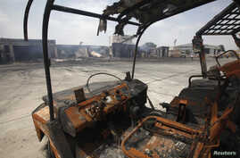 FILE - Damaged vehicles are left on the tarmac of Jinnah International Airport, after Sunday's attack by Taliban militants, in Karachi, June 10, 2014.