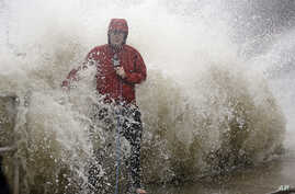 A news reporter doing a stand up near a sea wall in Cedar Key, Fla., is covered by an unexpected wave as Hurricane Hermine nears the Florida coast, Sept. 1, 2016.