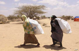 Southern Somali women carry food aid donations from the UNHCR, as they make their way to their refugee camp in Dollow, Somalia, Tuesday. Aug. 30, 2011.  Despite the drought and famine, refugees in Somalia are celebrating the Muslim holiday of Eid al-