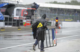 A member of the team of Moto3 rider Vicente Perez of Spain carries some gear on the pit lane as the track remains closed for the British Motorcycle Grand Prix at the Silverstone racetrack in Silverstone, England, Sunday, Aug. 26, 2018. The start of t