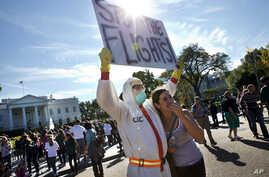 Jeff Hulbert, left, of Annapolis, Maryland, protests U.S. handling of Ebola cases, as Mary Wills, right, of Cleveland, playfully covers her face while taking a photo with Hulbert, outside of the White House, Oct. 17, 2014.