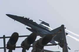 This U.S. Navy photo obtained Sept. 24, 2014 shows an F/A-18F Super Hornet attached to the Fighting Black Lions of Strike Fighter Squadron (VFA) 213 as it flies over the aircraft carrier USS George H.W. Bush.
