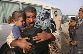 Abdul Rahman Ismail, an Iraqi soldier who has been targeted by Islamic State extremists who destroyed his house two years ago, is reunited with his family after they were able to flee their Islamic State held town, as displaced Iraqi families gather