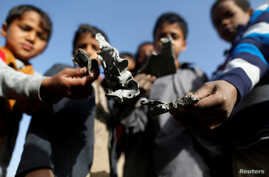 Boys hold missile shrapnel they collected from the site of a Saudi-led air strike in the Houthi-held capital Sanaa, Yemen, Jan. 20, 2019.