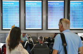 Passengers check arrival and departure displays at O'Hare International Airport in Chicago, Illinois, Sept. 27, 2014.
