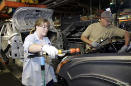 FILE - A female employee works alongside a male colleague at a Ford Motor Plant in Wayne, Michigan.