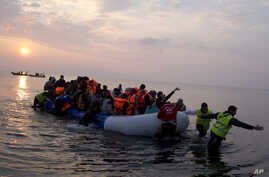 Volunteers help migrants and refugees on a dingy as they arrive at the shore of the northeastern Greek island of Lesbos, after crossing the Aegean sea from Turkey, March 20, 2016.
