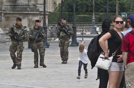 French soldiers patrol by the glass pyramid at the Louvre museum in Paris, Aug. 18, 2016.