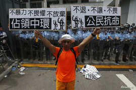 "A protester holds up placards which reads ""Occupy Central"" (L) and ""Civil Disobedience"" in front of a line of riot police outside government headquarters in Hong Kong, Sept. 27, 2014."