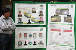 """A journalist looks at posters detailing the arrest operation of a suspect in the death of U.S. Drug Enforcement Administration Special Agent James """"Terry"""" Watson, in Bogota, Colombia, June 25, 2013."""