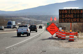 FILE - Construction signs warn drivers of lane closures along US Route 550 as crews prepare to begin work on the highway in Bernalillo, N.M., Feb. 19, 2015.